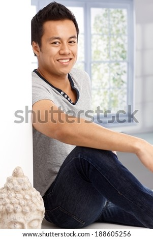 Portrait of happy young man at home, looking at camera, sitting front of window. - stock photo