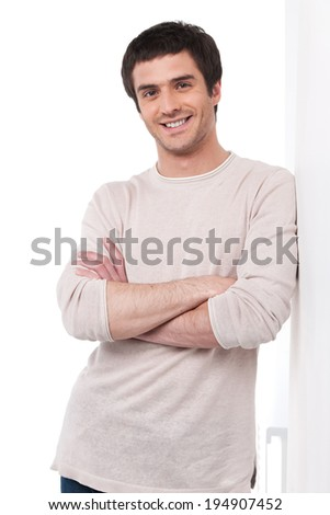 portrait of happy young man leaning on wall. handsome guy standing and folded hands
