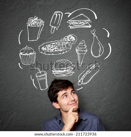 portrait of Happy young man looking up thinking what to eat. fast food concept - stock photo