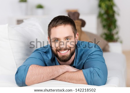 Portrait of happy young man lying on sofa in house