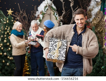 Portrait of happy young man pointing at Christmas present with family standing in background at store - stock photo