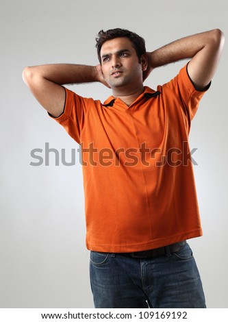 portrait of happy young  man relaxing with hands behind head