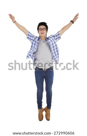 Portrait of happy young man with casual clothes, jumping in the studio enjoy his freedom - stock photo