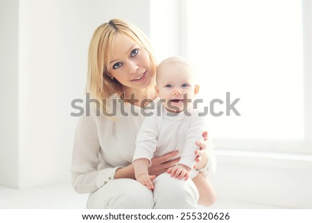 Portrait of happy young mom with baby at home in white room  - stock photo