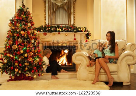 Portrait of happy young mother with child reading book on Christmas evening. Classic interior with a Christmas tree and a fireplace.