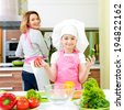 Portrait of happy young mother with daughter in pink apron cooking at the kitchen. - stock photo