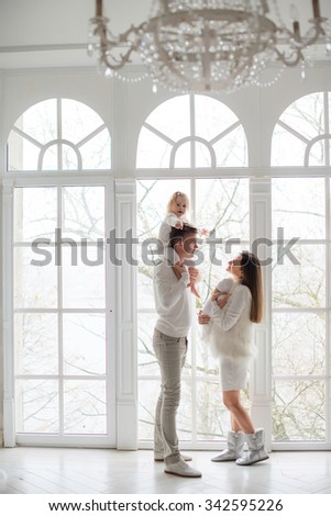 Portrait of happy young parents with baby  at home. - stock photo
