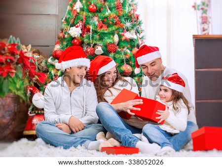 Portrait of happy young parents with their two precious kids are considered gifts, sitting on the floor near festive Christmas tree
