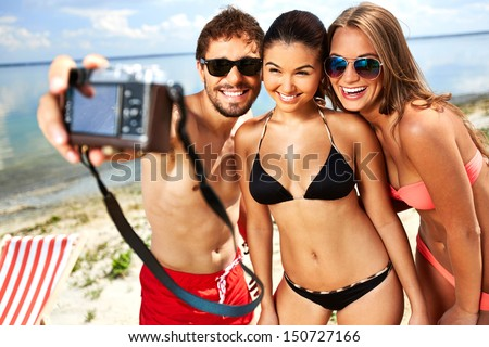 Portrait of happy young people having fun on the beach - stock photo