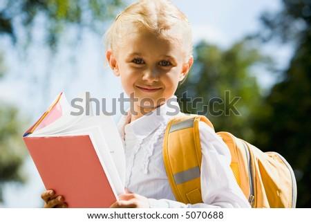 Portrait of happy young schoolgirl looking at camera - stock photo