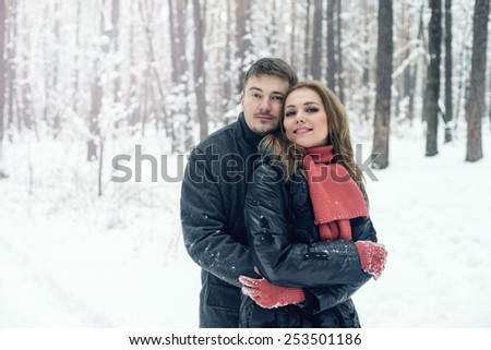 Portrait of happy young woman and her boyfriend in winter park