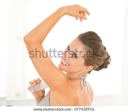 Portrait of happy young woman applying deodorant on underarm - stock photo
