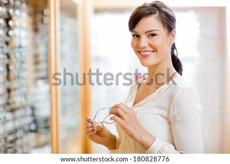 Portrait of happy young woman buying glasses in optician store - stock photo