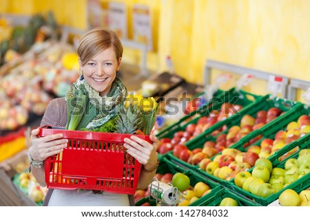 Portrait of happy young woman carrying shopping basket in grocery store - stock photo