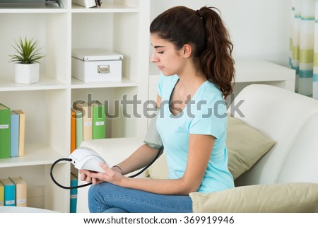 Portrait of happy young woman checking blood pressure while sitting on sofa at home