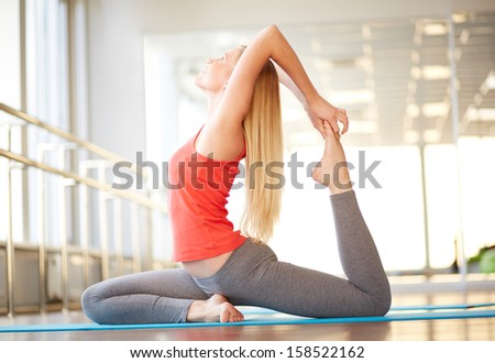 Portrait of happy young woman doing stretching exercise in gym - stock photo