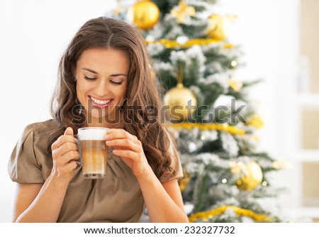 Portrait of happy young woman drinking latte macchiato near christmas tree - stock photo