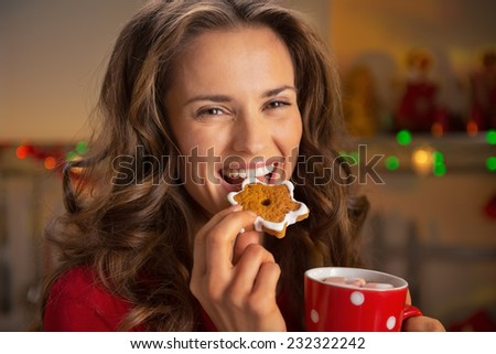 Portrait of happy young woman eating christmas snacks - stock photo