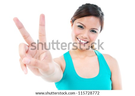 Portrait of happy young woman giving peace sign over white background - stock photo