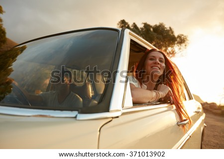 Portrait of happy young woman going on a road trip leaning out of window. Female enjoying travelling in a car with her boyfriend. - stock photo