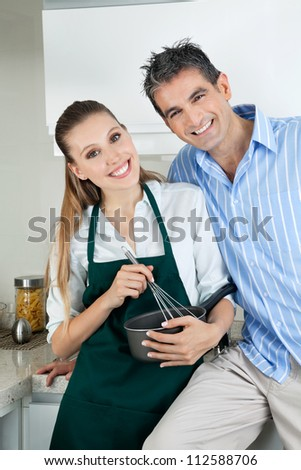 Portrait of happy young woman holding pan and whisk while standing with boyfriend in kitchen