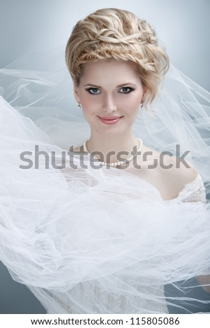portrait of happy young woman in wedding dress posing with white bridal veil - stock photo