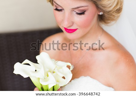 portrait of happy young woman in white wedding dress and bridal veil with flowers. - stock photo