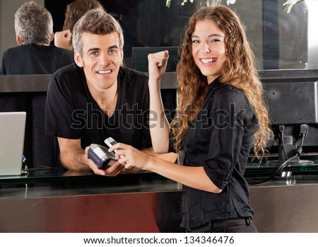 Portrait of happy young woman paying with mobilephone over electronic reader and hairdresser at salon counter