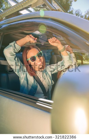 Portrait of happy young woman raising her arms and having fun inside of car in a road trip adventure. Female friendship and leisure time concept. - stock photo