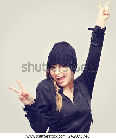 Portrait of happy young woman raising her arms and showing victory sign - stock photo
