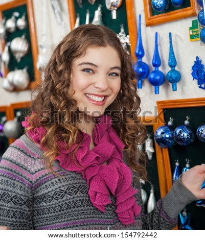 Portrait of happy young woman shopping ornaments in Christmas store