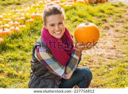 Portrait of happy young woman showing pumpkin - stock photo