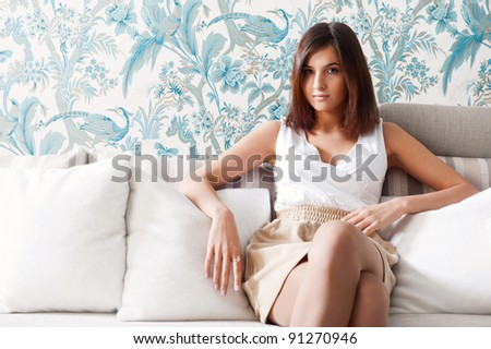 Portrait of happy young woman sitting on sofa at her home - stock photo