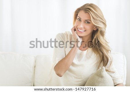 Portrait of happy young woman sitting on sofa at home - stock photo