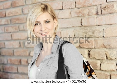 Portrait of happy young woman standing front of brick wall, looking at camera.