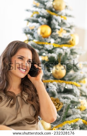 Portrait of happy young woman talking cell phone near christmas tree - stock photo