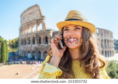 Portrait of happy young woman talking mobile phone in front of colosseum in rome, italy - stock photo