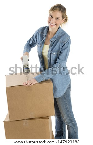 Portrait of happy young woman taping cardboard boxes against white background
