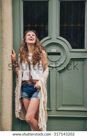 Portrait of happy young woman wearing boho clothes standing outside buildings in street - stock photo