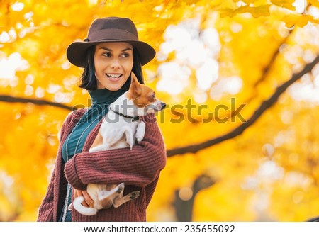Portrait of happy young woman with dog outdoors in autumn looking on copy space - stock photo