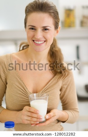 Portrait of happy young woman with glass of milk in kitchen - stock photo
