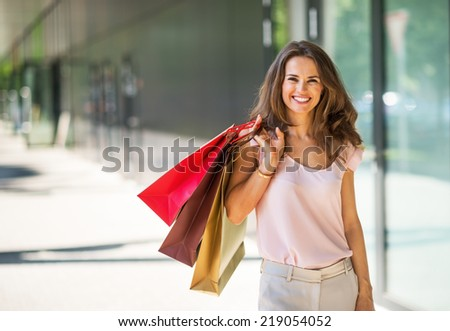 Portrait of happy young woman with shopping bags on the mall alley - stock photo