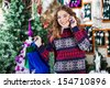 Portrait of happy young woman with shopping bags using cellphone in Christmas store - stock
