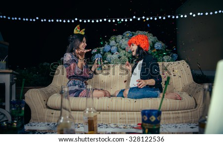 Portrait of happy young women friends with costumes and atrezzo having fun among the colorful confetti cloud in a outdoors party. Friendship and celebrations concept. - stock photo