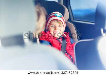 Portrait of hapy little kid boy sitting in car. Child in safety car seat with belt. Safe travel with kids and traffic laws concept. - stock photo