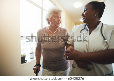 Portrait of healthcare worker and senior woman walking together. Nurse assisting senior female patient while walking in nursing home. - stock photo
