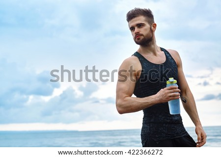 Portrait Of Healthy Athletic Man With Fit Body Holding Bottle Of Refreshing Water, Resting After Workout Or Running At Beach. Thirsty Male With A Drink After Outdoor Training. Sports, Fitness Concept - stock photo