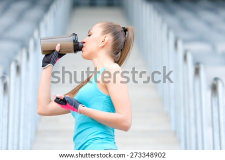 Portrait of healthy fitness girl drinking protein shake. Woman drinking sports nutrition beverage while working out  - stock photo