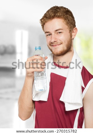 Portrait of healthy fitness man drinking a bottle of water - stock photo