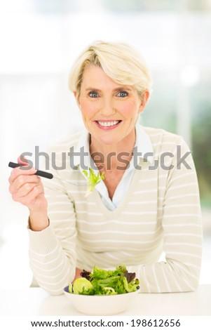 portrait of healthy senior woman having vegetable salad - stock photo